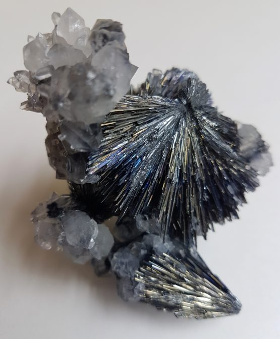 Stibnite on Quartz with two beams of acicular radiating crystals in a delicate contrast with the withe matrix.