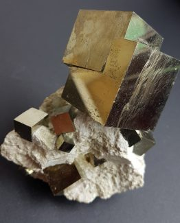 Large Pyrite twinned crystal with small cubic crystals spread over the matrix.