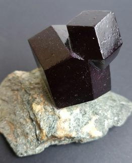 Perfectly defined Almandine Garnet crystal twin on matrix.