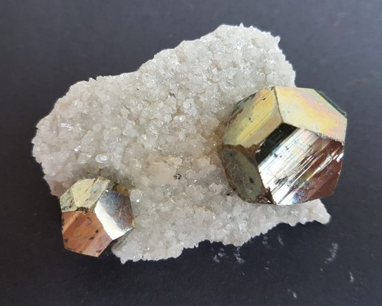 Two isolated pentagonododecahedral crystals of Pyrite on Quartz matrix